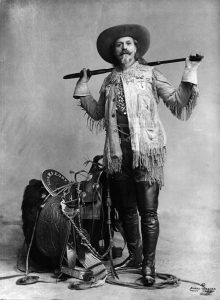 Buffalo Bill posing in front of saddle